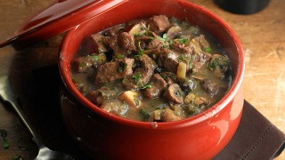 Beef casserole with chesnuts, mushrooms and winter spice served in a casserole dish and sprinkled with parsley