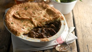 Beef and Chestnut Pie served in a white dish with some of the pastry removed to see the filling