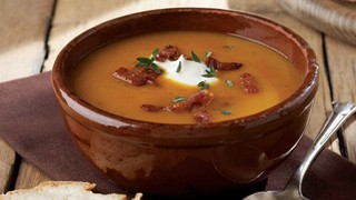 Butternut squash and smoked bacon soup served in a bowl topped with greek yoghurt and bacon bits