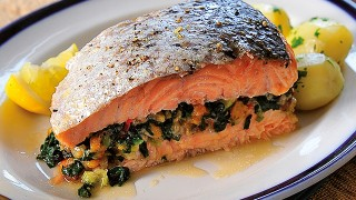 Carribean Salmon Fish served on a white plate with new potatoes and herbs