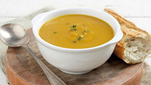 Carrot, Sweet Potato and Ginger soup served in a white bowl and crusty bread