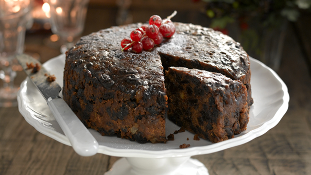 Christmas cake served on a white serving dish with a piece cut out