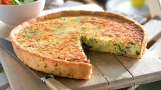 Crab and watercress quiche with a portion missing to see the inside