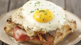 Croque Madame served with a fried egg on top and chives
