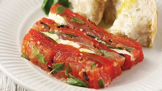 English Tomato and Burnt Red Pepper Terrine served on a white plate with a piece of crusty bread