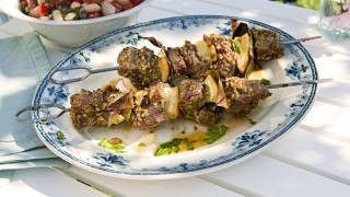 Pesto Marinated Lamb Kebabs served on a white and blue plate on an outdoor table