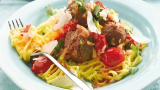 Mediterranean meatballs served with pasta and vegetables, topped with parmesan in a bowl