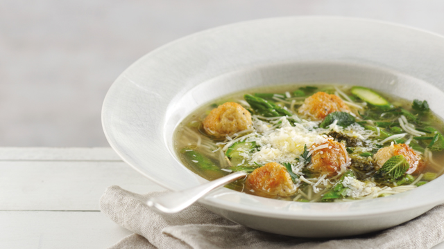 Spring Minestrone Soup with Chicken Meatballs served in a white dish with a sprinkling of parmesan
