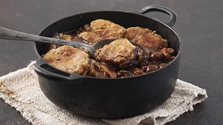 Minty Lamb Cobbler served in a casserole dish with a spoon lifting out the topping