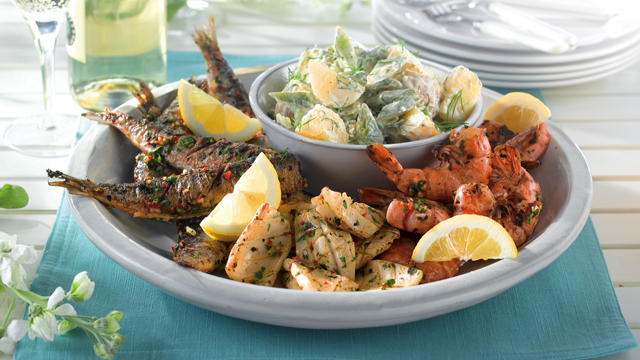 Bowl of mixed grilled fish including sardines, squid and king prawns with a bowl of new potato and runner bean salad