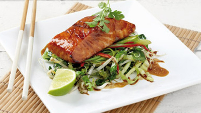 Oriental Style Salmon served with a lemon wedge on a white dish with chopsticks