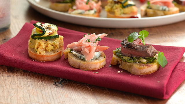 Three party crostinis served on a napkin in front of a platter of more crostinis.