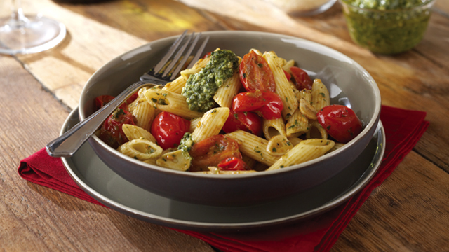 Penne pasta served with tomatoes, pesto, basil leaves in a grey dish