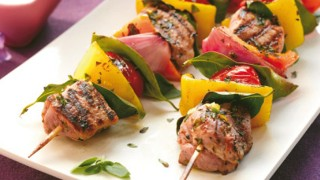 Mediterranean Pork Kebabs, served with orange and red peppers on plate