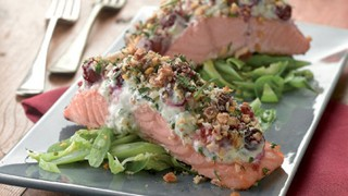 Salmon with a cranberry and walnut crust served on a bed of green vegetables