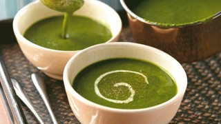 Spinach soup served in a bowl with a swirl of cream and black pepper