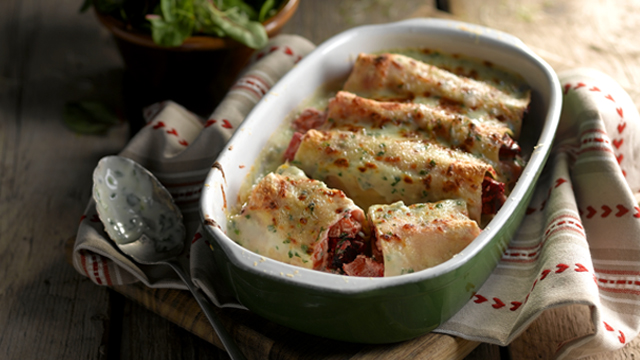 Vegetarian Cannelloni served in a green dish on top of a white and red towel