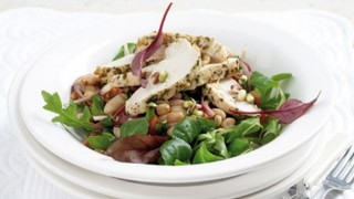 Warm chicken salad served in a white bowl with mixed leaves