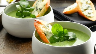 Watercress and Roast Garlic Soup Served with Roquefort Cheese Slices
