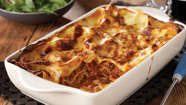 Beef lasagne cooked in a white dish with a portion missing