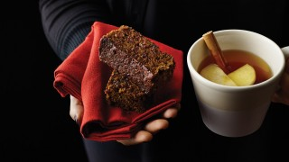 Bonfire Parkin cut up, served on a red napkin with a cup of hot mulled apple juice