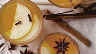 Warming Party Punch served in three glasses with apple slices, star anise and cinnamon sticks