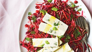 Beetroot and Pomegranate Slaw topped with slices of feta and dill on a white plate