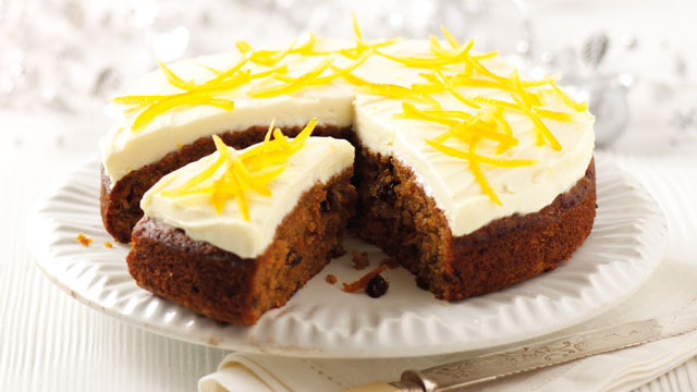 Old Fashioned Carrot Cake with Lemon and Cream Cheese Frosting served on a white plate with a slice cut to show the inside