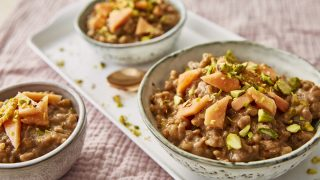 Chai Tea Rice Pudding served in white bowls, topped with pistachios and papaya slices