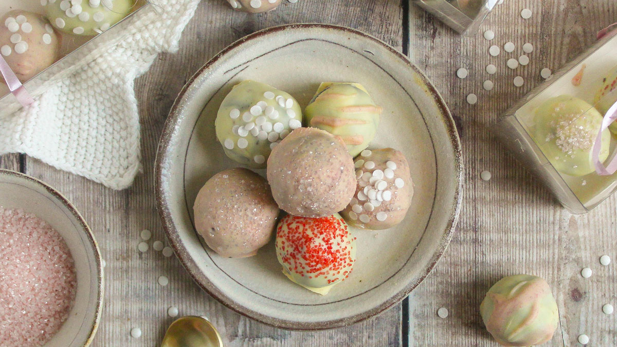 Cookie Cheesecake Truffles piled on top of each other on a rustic plate