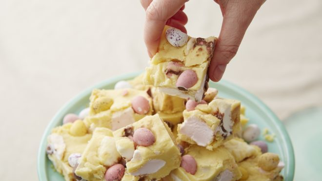 No Bake White Chocolate Mini Egg Rocky Road cut into squares and served on a turquoise plate