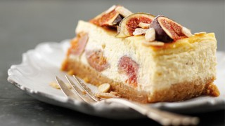 A slice of Baked Fig and Amaretto Cheesecake served on a white plate with a dessert fork