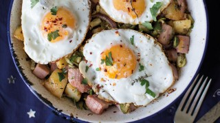 One-Pan Leftover Ham and Potato Hash served in a white and blue dish sprinkled with chilli flakes and coriander