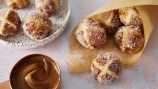 Hot Cross Bun Doughnuts wrapped in a brown paper cone, in a bowl, with a small pan of caramel sauce