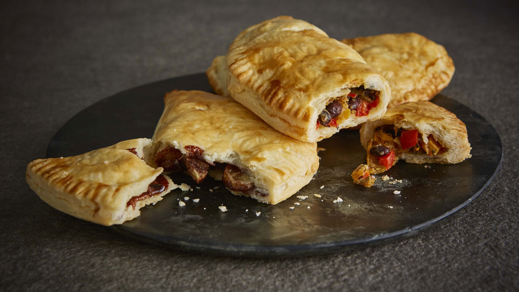 Butternut Squash, Peppers, Cheese and Beans Pasty served on a dark marble plate, sliced to see the filling