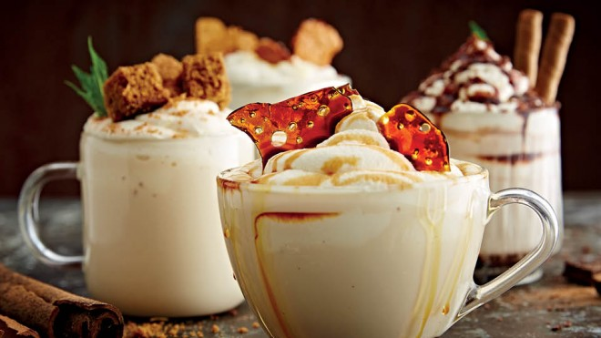 White Hot Chocolate served in glass cups with various toppings including caramel, cinnamon and biscuits