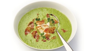 Chilled Yorkshire Pea, Watercress and Cumbrian Ham soup served in a white bowl and topped with a swirl of creme fraiche