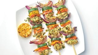 Fish Kebabs with Chermoula Sauce served on a white plate with a wedge of grilled lemon