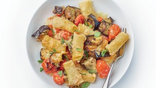 Roasted Tomato and Taleggio Pasta Bake served on a white plate and sprinkled with basil leaves