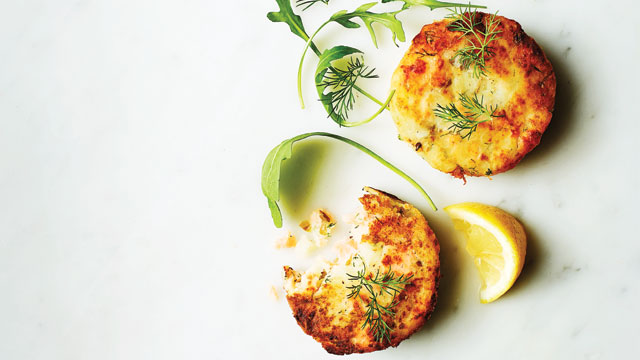 Smoked Salmon, Dill and Caper Fishcakes served on a marble slab with lemon wedges and rocket