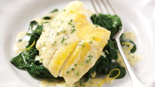 Smoked Haddock with Chive Butter Sauce on a bed of spinach in a white bowl