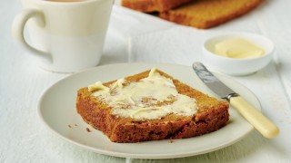 A slice of Granny Hilton's Sticky Bread on a white plate, with butter spread on top and next to a cup of tea