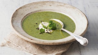 Chilled Yorkshire Pea, Watercress and Mint Soup served in a rustic grey bowl topped with crème fraiche and black pepper
