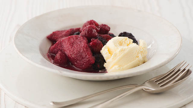 Summer Pudding with Clotted Cream Vanilla Ice Cream served in a white bowl with a fork and spoon to the side