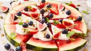 Watermelon Pizza sliced and topped with figs, strawberries and blueberries