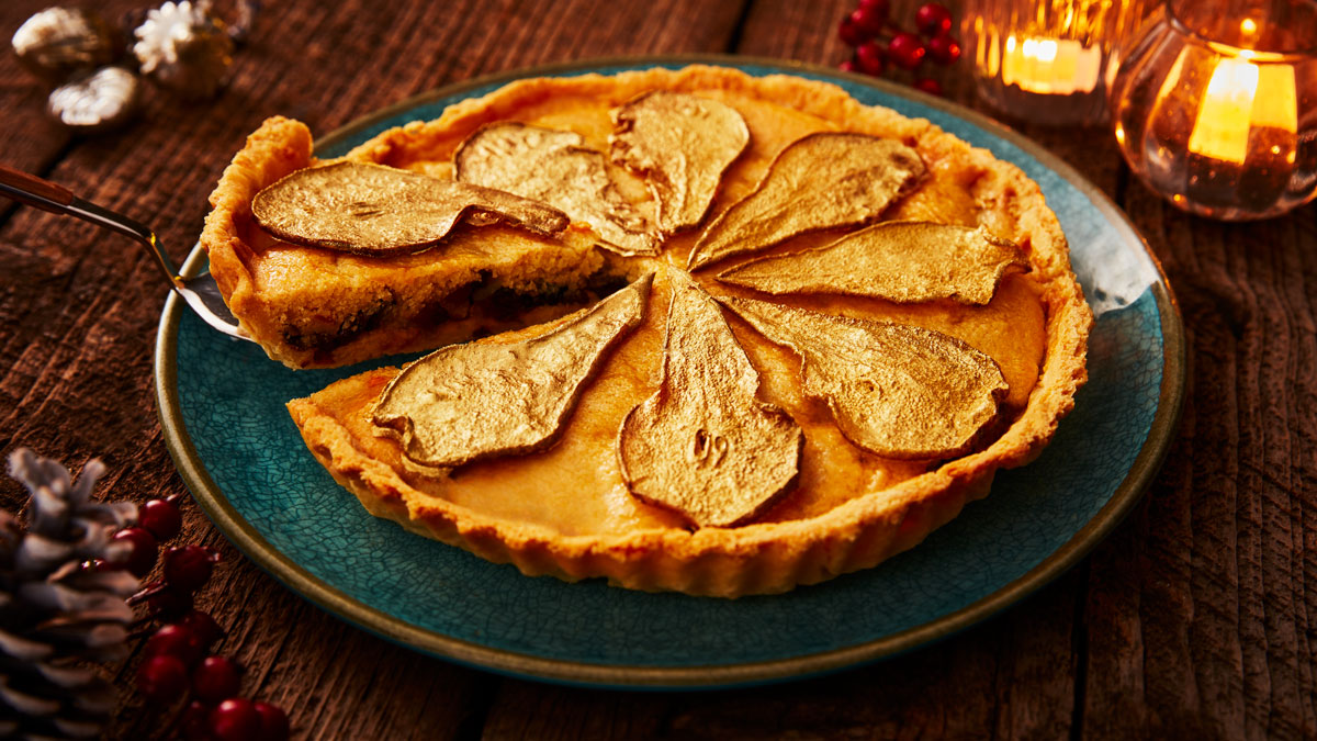 Festive Pear and Mincemeat Frangipane Tart, served on a blue plate with a slice being removed to see the filling
