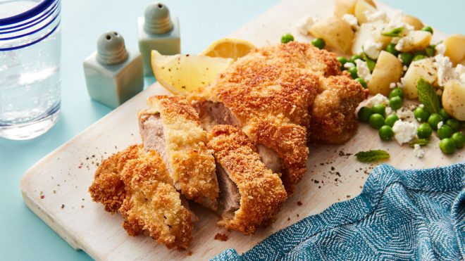Almond Pork Schnitzel sliced and served on a wooden board with new potatoes and peas