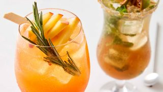 Aperol and Prosecco Peach Fizz served in a glass with ice and a sprig of rosemary