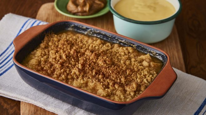 Salted Caramel Apple Crumble served in a blue dish, with a bowl of custard and a bowl of sauce behind