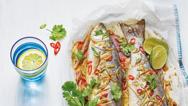Asian Style Grilled Fish served on baking paper topped with coriander and lime wedges